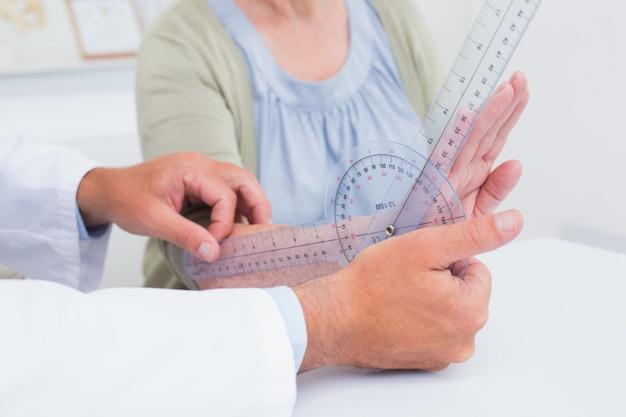 Fisioterapista che esamina i pazienti polso con goniometro