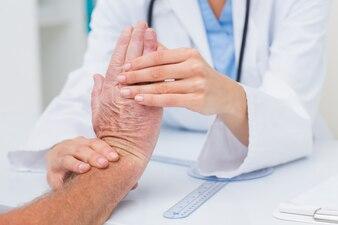 Fisioterapista che esamina il polso dei pazienti maschii
