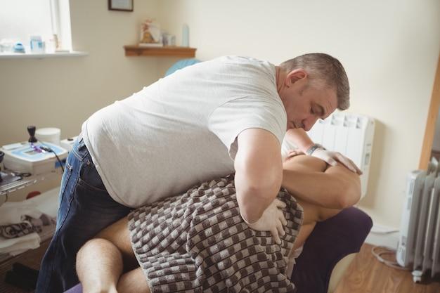 Fisioterapista che esamina indietro di un paziente