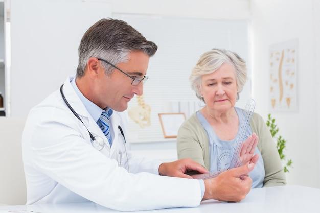 Fisioterapista che esamina polso della donna con goniometro