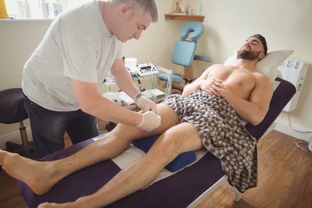 Fisioterapista che esegue aghi asciutti sul ginocchio di un paziente