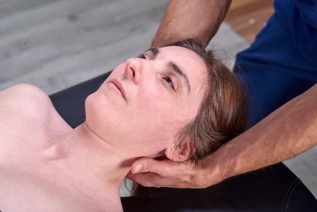 Fisioterapista che fa un collo di mobilizzazione del paziente femminile