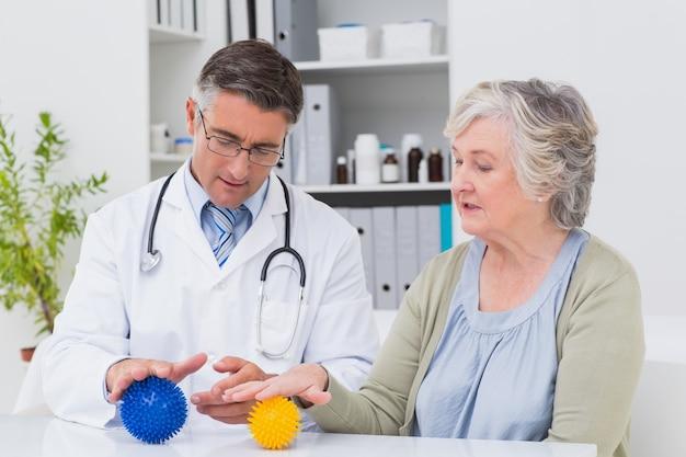 Fisioterapista che guida paziente femminile con la palla di massaggio