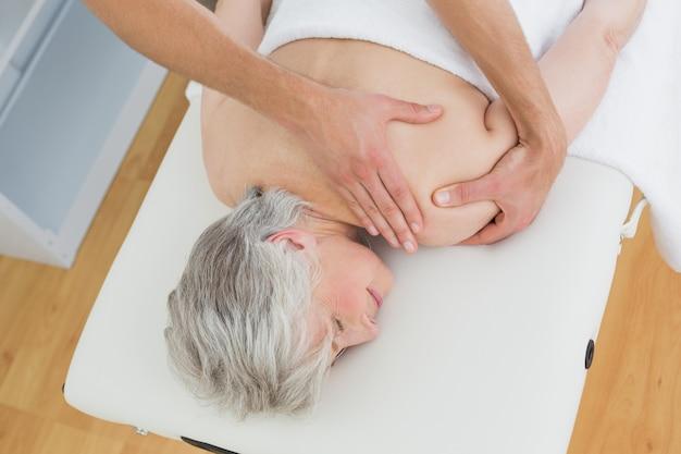 Fisioterapista che massaggia indietro un womans anziano