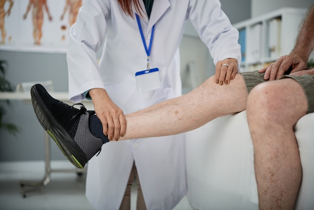 Fisioterapista che palpa la gamba