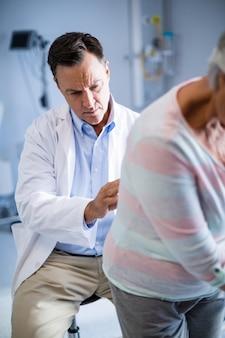 Fisioterapista che restituisce massaggio al paziente anziano