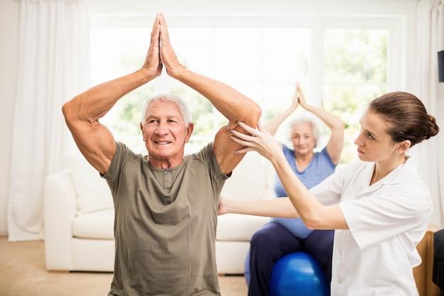 Fisioterapista che si prende cura dei pazienti anziani malati a casa