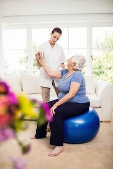 Fisioterapista che si prende cura del paziente anziano malato a casa