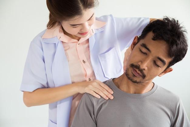 Fisioterapista che sta curando il trattamento sul collo dell'uomo