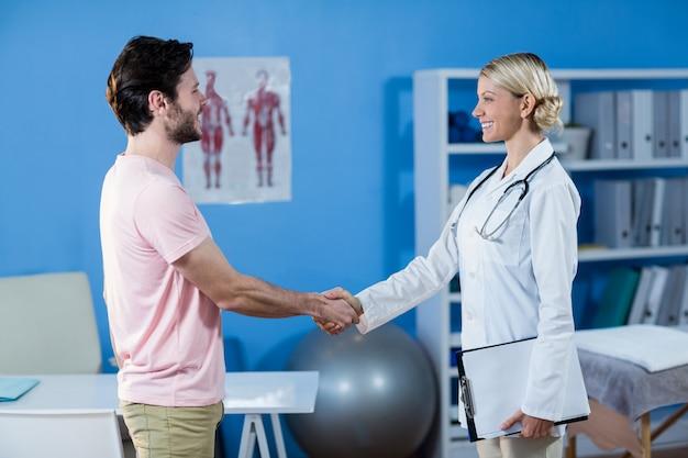 Fisioterapista che stringe le mani con il paziente maschio