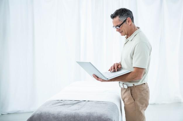 Fisioterapista che utilizza computer portatile nella sua clinica