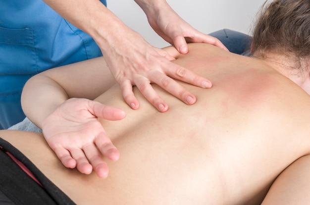 Fisioterapista, chiropratico che dà un massaggio e un allungamento di sottoscapolare e romboide