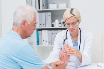 Fisioterapista femminile che esamina il polso dei pazienti maschii