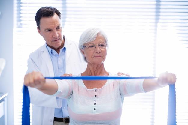 Fisioterapista maschio che dà massaggio della spalla alla donna senior
