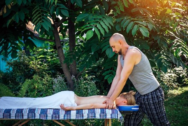 Fisioterapista maschio del massaggiatore che fa massaggio posteriore di benessere in giardino verde su aria fresca