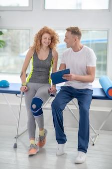 Fisioterapista maschio e paziente femminile che si siedono sullo strato, esaminando le note, sorridenti