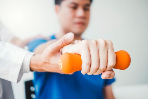 Fisioterapista uomo dando esercizio con il trattamento con manubri informazioni su braccio e spalla concetto apy