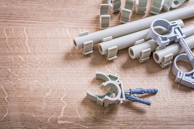 Fissatori e tubo del polipropilene della grande composizione di vista aerea con le clip sul bordo di legno