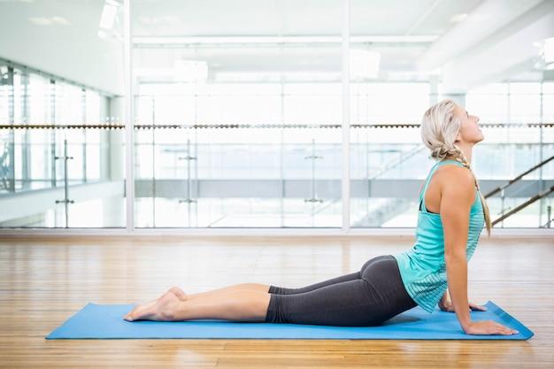 Fit bionda facendo yoga sulla stuoia in studio