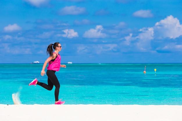 Fit giovane donna che corre lungo la spiaggia tropicale nel suo abbigliamento sportivo