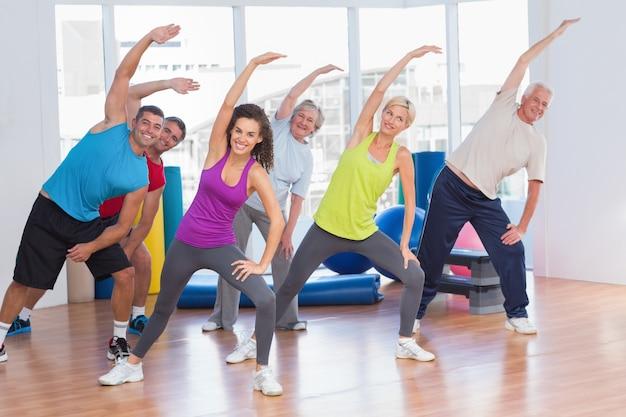 Fit persone che fanno esercizio di stretching in palestra