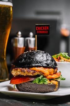 Fitburger di pollo vista laterale su un panino nero con un bicchiere di birra