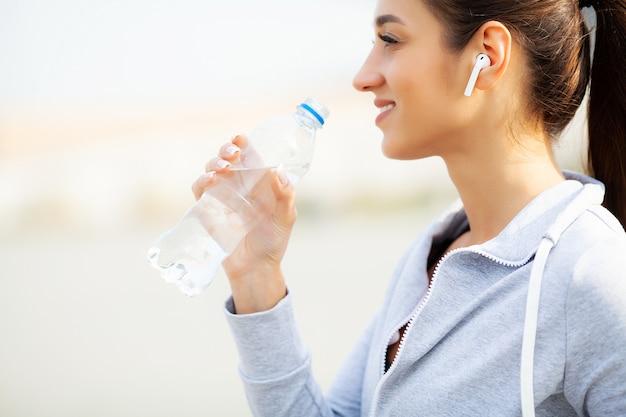 Fitness. acqua potabile della bella donna ed ascoltare la musica dopo avere corso
