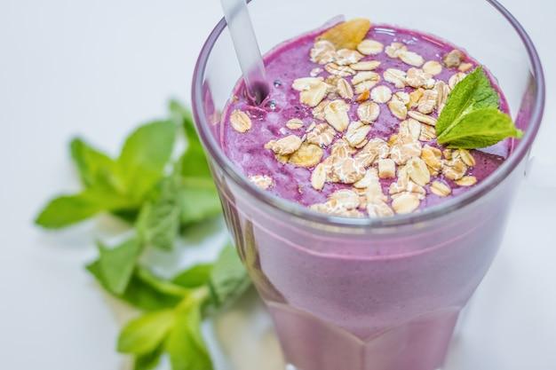 Fitness, concetto di stile di vita sano. ottimo per palestra, sport, delizioso cocktail fitness ai frutti di bosco con avena, farina d'avena con menta. yogurt e frutta per gli atleti. dieta