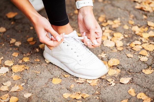 Fitness, corridore femminile legando le scarpe preparando per fare jogging