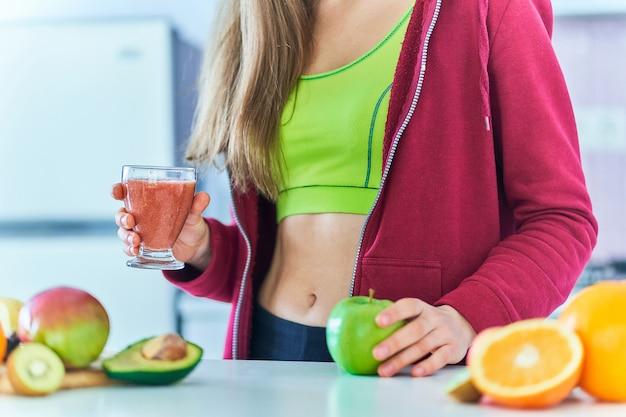 Fitness dieta femminile in abbigliamento sportivo beve un frullato di frutta fresca per perdere peso. bevande vitaminiche biologiche per un'alimentazione sana