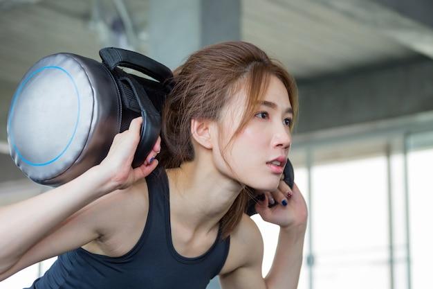 Fitness, donna asiatica in esercizi di allenamento con borsa pesata allenamento 10 kg