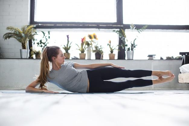 Fitness. donna di yoga che si estende a casa.