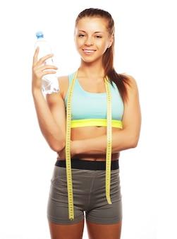Fitness e palestra. giovane donna sorridente con acqua.