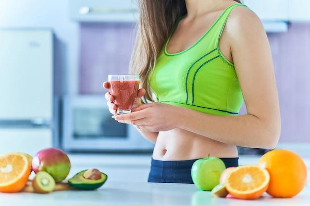 Fitness femminile in abbigliamento sportivo beve un frullato di frutta fresca per perdere peso. bevande dietetiche con vitamine per un'alimentazione sana