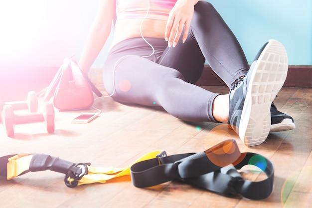 Fitness femminile riposo e rilassante dopo allenamento. donna seduta sul pavimento di legno. sport, fitness, concetto di stile di vita sano