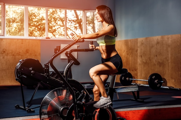 Fitness femminile usando air bike per allenamento cardio in palestra crossfit.