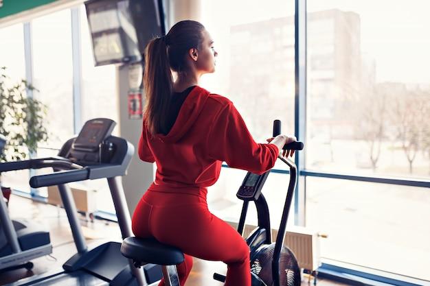 Fitness femminile usando air bike per allenamento cardio in palestra.