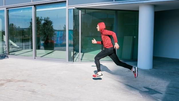 Fitness giovane corridore maschio in esecuzione all'esterno dell'edificio