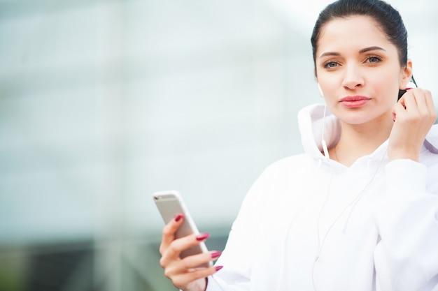 Fitness. musica d'ascolto della donna sul telefono mentre esercitandosi all'aperto - sport e concetto sano di stile di vita