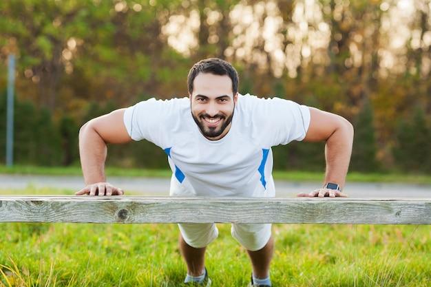 Fitness nel parco. giovane e sportivo allenamento all'aria aperta in abbigliamento sportivo. sport, salute, atletica.