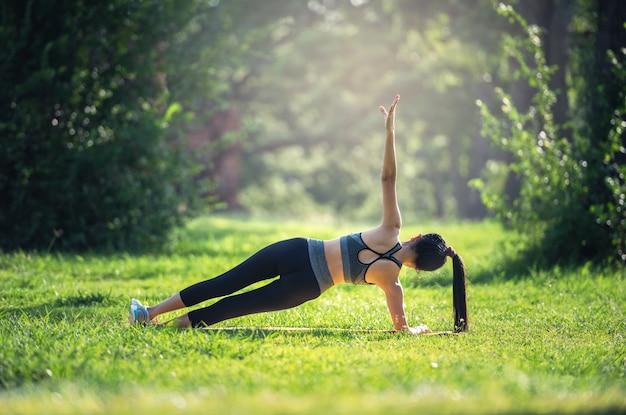 Fitness, sport concetto di stile di vita facendo esercizi di yoga su stuoie all'aperto