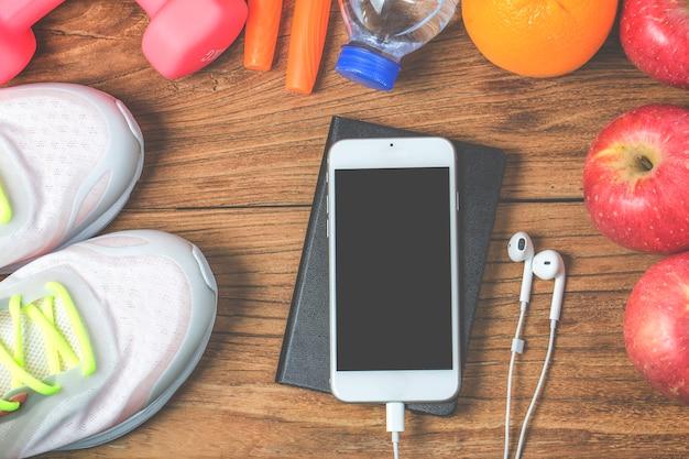 Fitness, stile di vita sano e attivo concetto, bottiglia d'acqua, manubri, scarpe sportive, smartphone con cuffie e mele su sfondo di legno. copia spazio per il testo. vista dall'alto