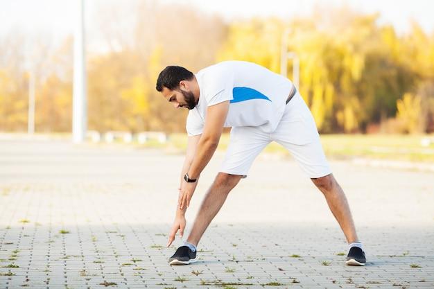 Fitness. stretch uomo che fa esercizio di stretching. in piedi in avanti si allungano le gambe
