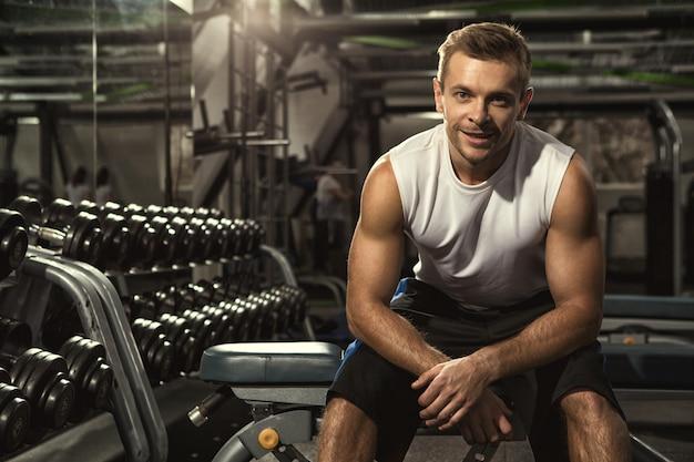 Fitness uomo seduto rilassato in palestra dopo il suo allenamento sorridendo con gioia