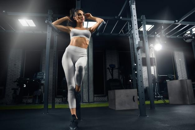 Fitnesswoman in posa in palestra.