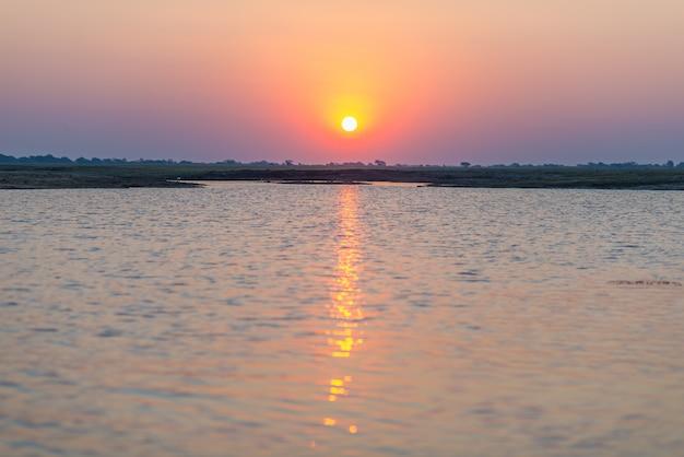 Fiume chobe in controluce al tramonto. scenic luce solare colorata all'orizzonte.