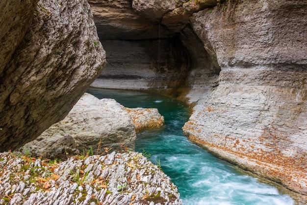 Fiume di montagna con acqua color smeraldo in una gola di pietra