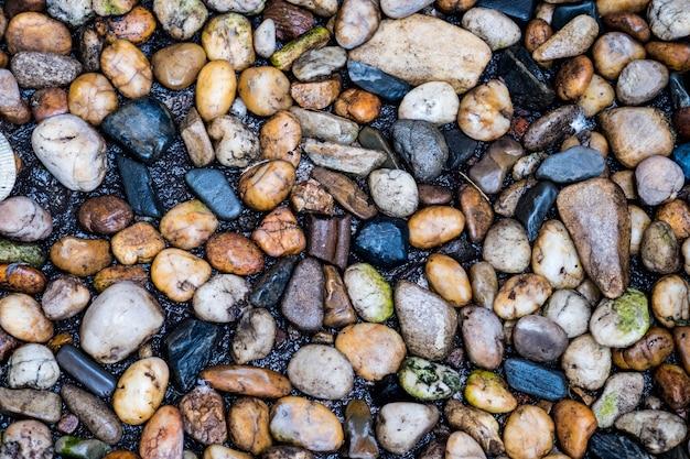 Fiume di pietra, ciottoli colorati. piccole pietre pulite sul terreno.