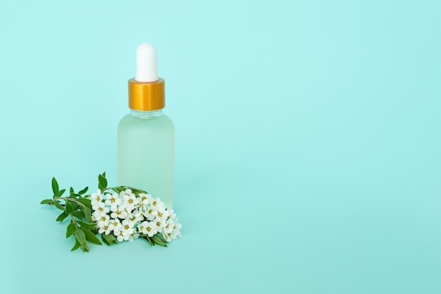 Flacone cosmetico in vetro con olio. contenitore con piccoli fiori bianchi. barattolo cosmetico.
