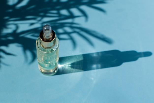 Flacone di vetro contagocce con olio cosmetico o siero, luce naturale dura